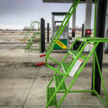 semi truck ladder sits at fuel rack in winter.
